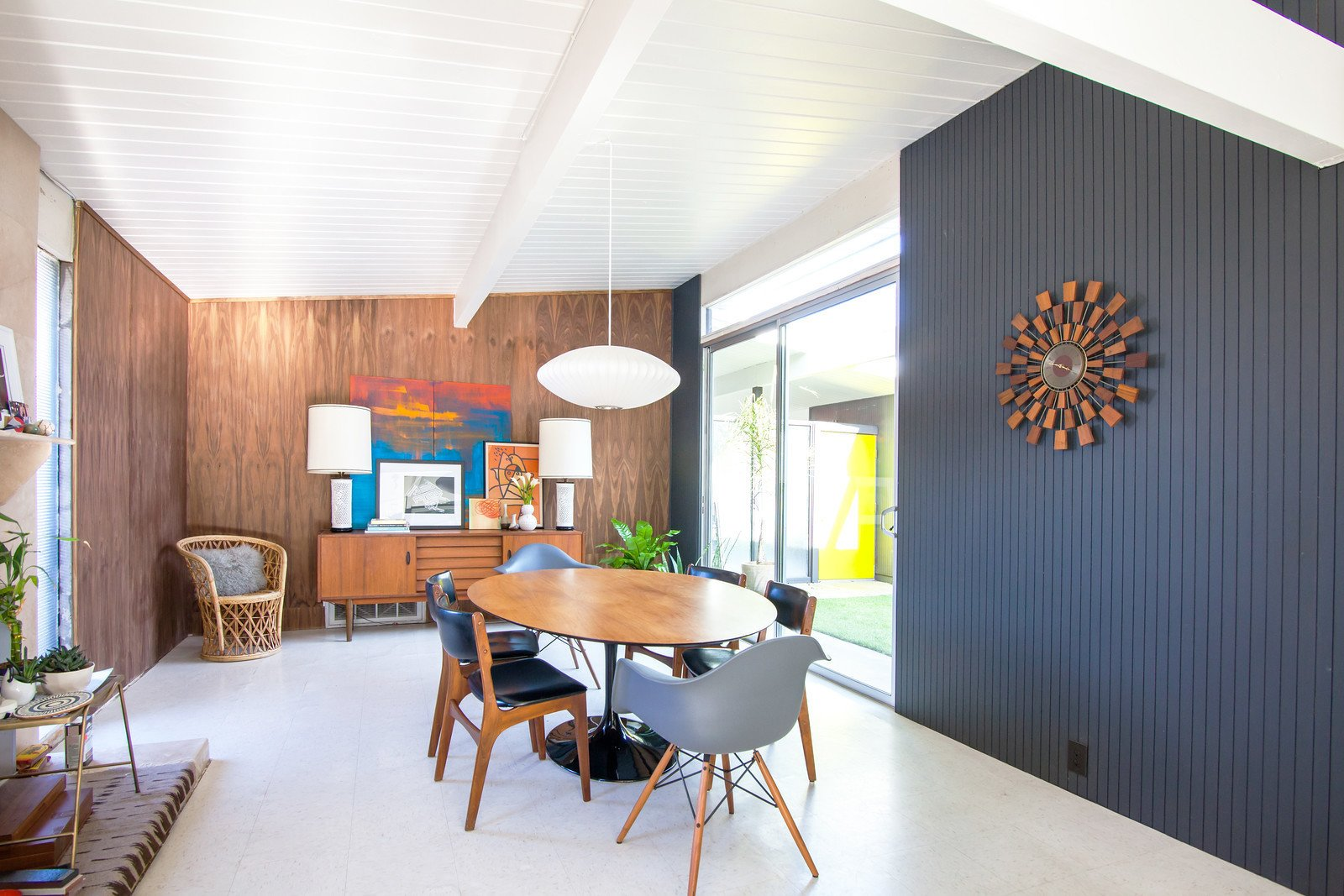 A Nelson Saucer Pendant Lamp by George Nelson hangs over the dining table with Eames Molded Plastic armchairs to compliment the surrounding set of chairs.