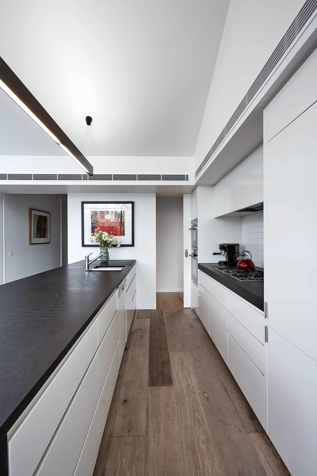 The streamlined kitchen features Miele cooktop, Sirius hood, Siemens oven, and Fisher & Paykel refrigerator.  127+ Inspiring Interior Ideas by Dwell from Just Redo It: A Home Near Melbourne Takes Another Stab at a Dated '80s Addition