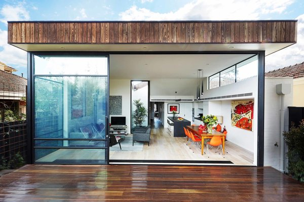 """The dramatic rear elevation showcases the open-plan living and dining room. Apart from the addition, the rest of the home maintained its """"traditional"""" layout, with bedrooms branching off from a central hallway. Windows on all sides of the addition bring light in and make the space feel bright and expansive. Tonal and textural contrast can be seen between the burnt ash cladding at the exterior and the engineered European oak flooring at the interior. Through thoughtful design and space planning, the architects and owners made the biggest impact possible with only 500 square feet of added living space."""