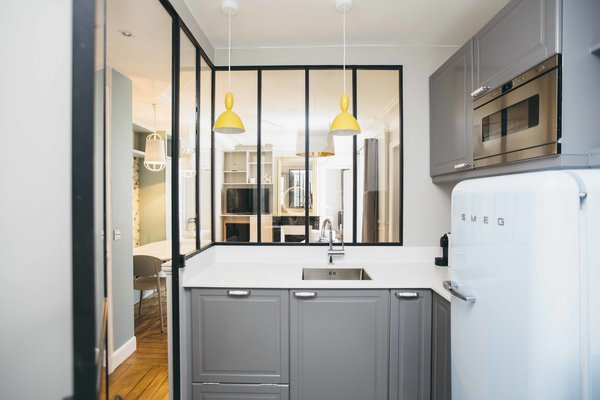 The window partition motif is repeated in the kitchen, allowing for communication between kitchen and living area. Gray cabinetry and white Silestone counters fit in alongside vibrant yellow pendants by MUUTO and a retro, light-blue Smeg refrigerator.
