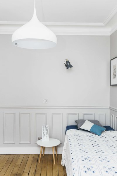 The second bedroom, shared by two young children, offers a private space away from the rest of the home. The owners and architect alike made sure to maintain the apartment's original features, including the ceiling moldings.