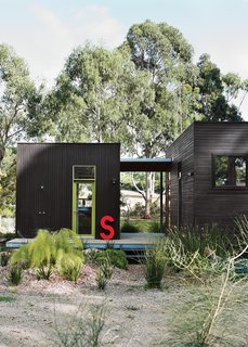 15 Modern Homes with Black Exteriors - Photo 8 of 15 - For her family's house near Melbourne, Anna Horne created a series of prefab wood modules using a design from the company Prebuilt. She found the old industrial letter at a factory; it stands for Somerset, the name of the house.
