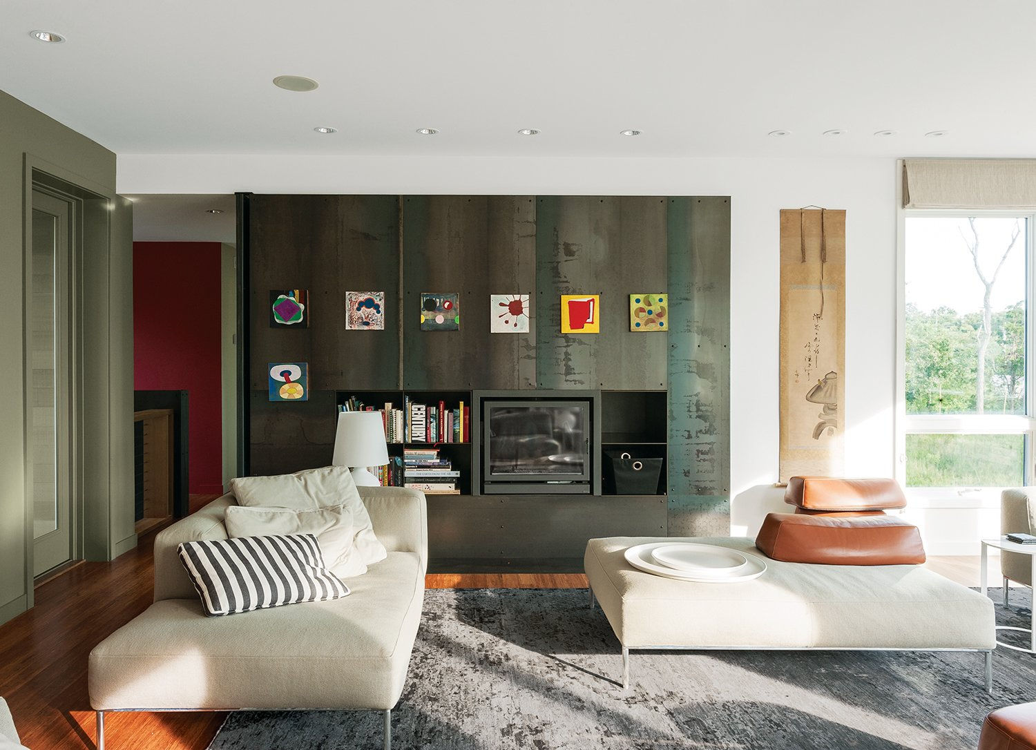 The fireplace wall, a Resolution: 4 signature, is made of 14-gauge hot-rolled steel panels with storage components in one-eighth welded steel. On one side is a pivoting privacy panel that allows the guest wing to be closed off. Art attaches to the metal with magnets. Tagged: Living Room, Medium Hardwood Floor, Sofa, Ceiling Lighting, and Recessed Lighting.  Photo 5 of 11 in An Unconventional Prefab on Fishers Island