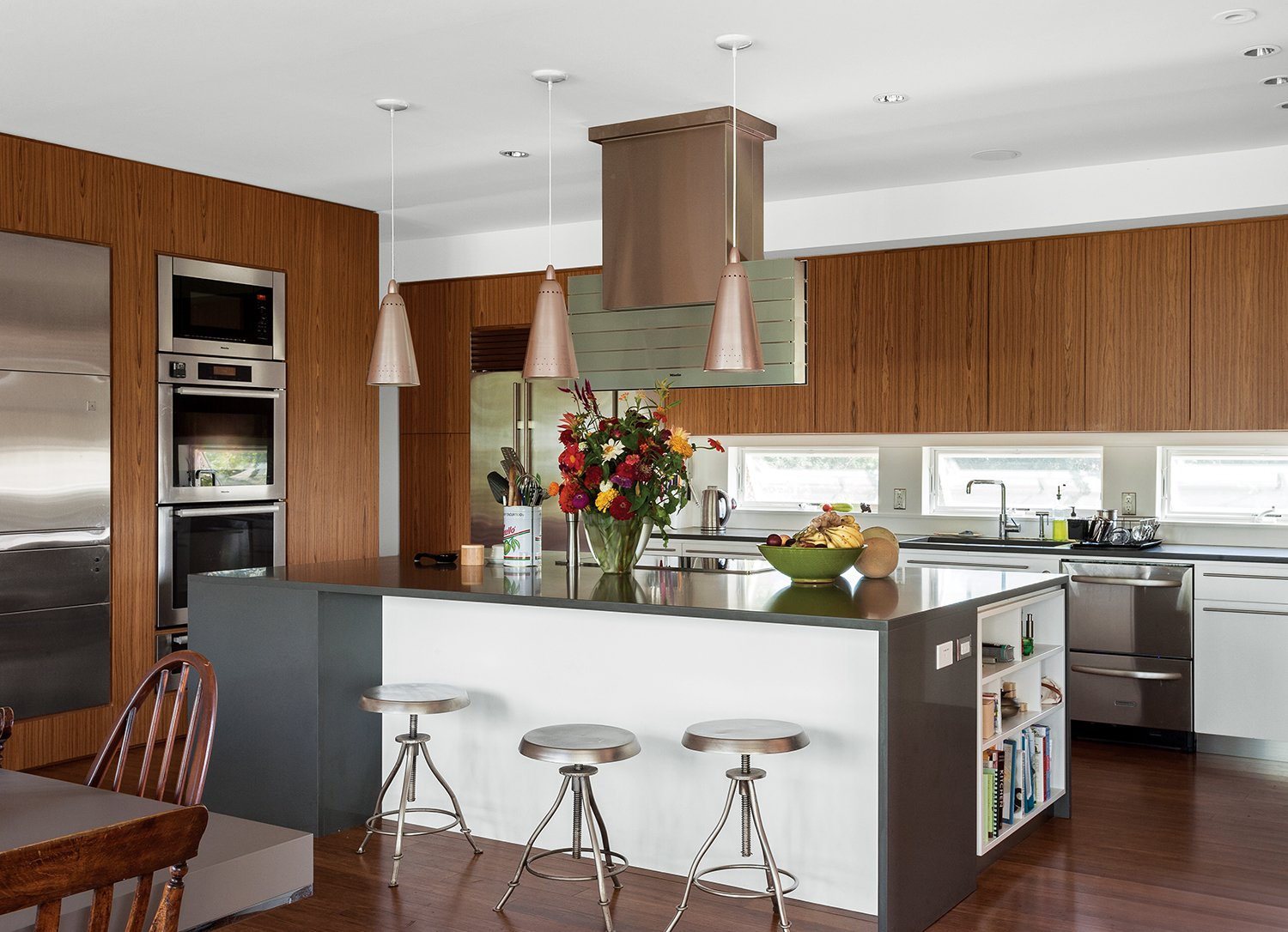 In the kitchen, teak-and- thermofoil cabinets and Caesarstone countertops mix with Miele appliances—wall ovens, induction cooktop, hood, and microwave—and a Sub-Zero refrigerator. The kitchen sink and faucet are by Blanco. The owners, who split their time between Fishers Island and Great Britain, found the vintage pendant lamps at Lassco architectural salvage.