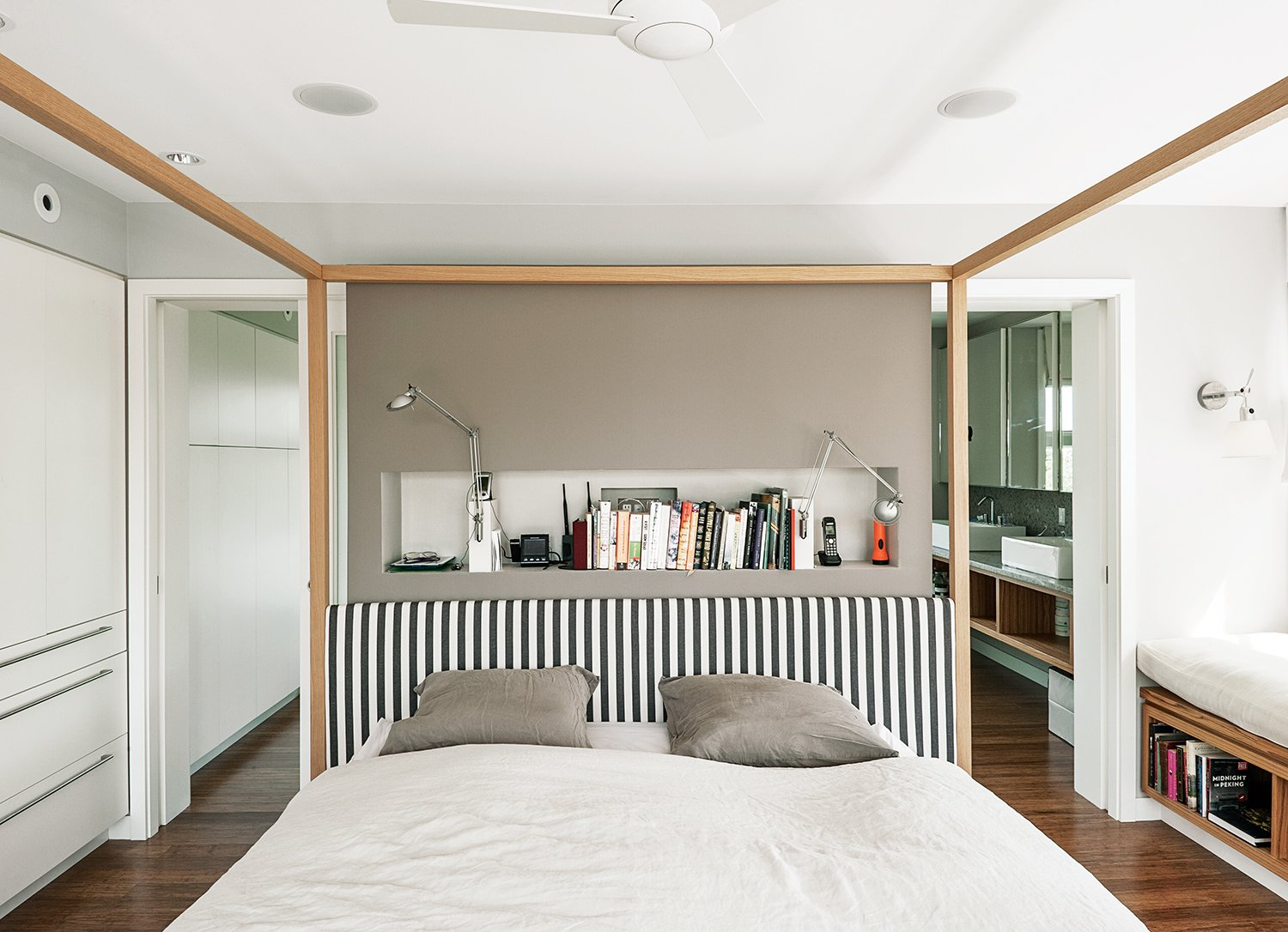 An Alcova bed from B&B Italia dominates the master bedroom. A niche behind the bed holds Berenice wall lamps by Luceplan, and the walls are painted in Cornforth White and Charleston Gray from Farrow & Ball. Tagged: Bedroom, Bed, and Medium Hardwood Floor.  Photo 8 of 11 in An Unconventional Prefab on Fishers Island