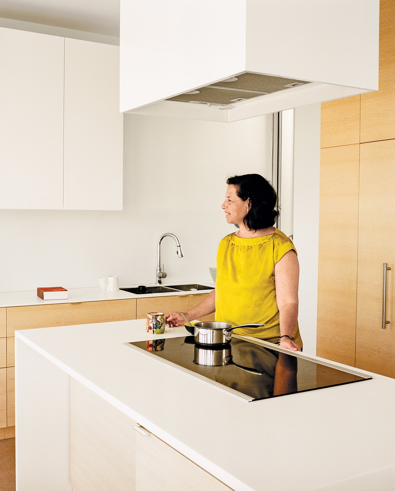 The kitchen has a Bosch induction range and hood surrounded by a box made by the architect. The faucet is by Blu Bathworks.  Photo 5 of 7 in A Modern Multiunit Prefab Prototype in Vancouver