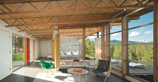 The architects wrapped the glazing around the corner of the living room to bring the landscape inside. The open-web trusses run continuously from indoors to out. A fleet of Modernica furnishings complement a Prototype Boomerang chair by Richard Neutra, a custom Moufelt industrial felt rug, and Circa50 butterfly chairs.