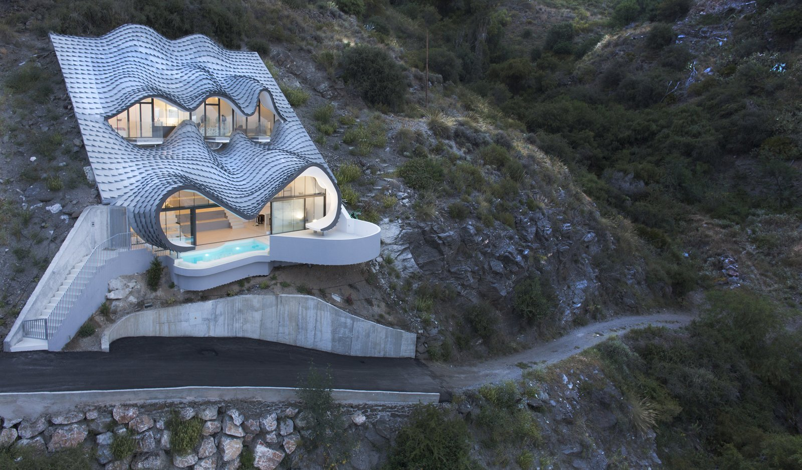 "GilBartolomé Architects says the metal facade looks like ""the skin of a dragon set in the ground when seen from below"" but ""waves of the sea when seen from above."" Tagged: Exterior, House, and Curved RoofLine.  Mediterranean by Heather Corcoran from Cliff House"