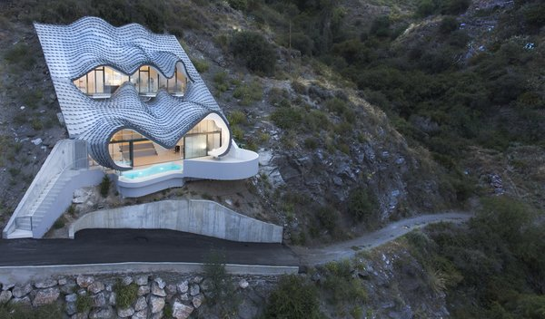 "GilBartolomé Architects says the metal facade looks like ""the skin of a dragon set in the ground when seen from below"" but ""waves of the sea when seen from above."" Photo  of Cliff House modern home"