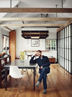 10 Ways to Solve Storage Problems in Small Spaces - Photo 9 of 10 - Here, homeowner Vincent Kartheiser is seated in his kitchen. Behind him, you can see the bed raised to the ceiling and the huge slab of redwood that served as a headboard, is now flipped down to create a bar-height desk. Making key elements to double duty, such as the head board/desk, are trademark qualities of small spaces done right.
