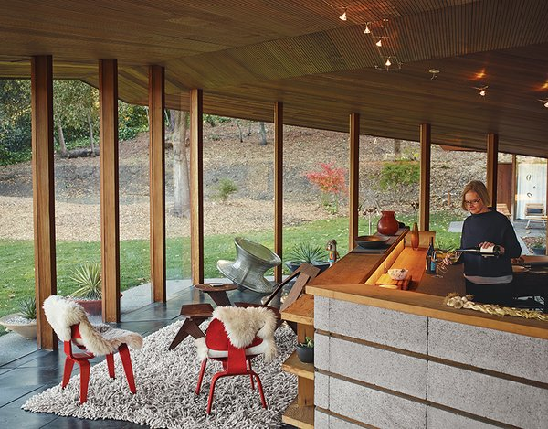 The Midcentury Home That Maintains Its Quirkiness After All These Years - Photo 3 of 9 - Lambert pours wine in the kitchen, which is defined by a low concrete-block wall and serves as the home's central core. The seating-area chairs are from Herman Miller.