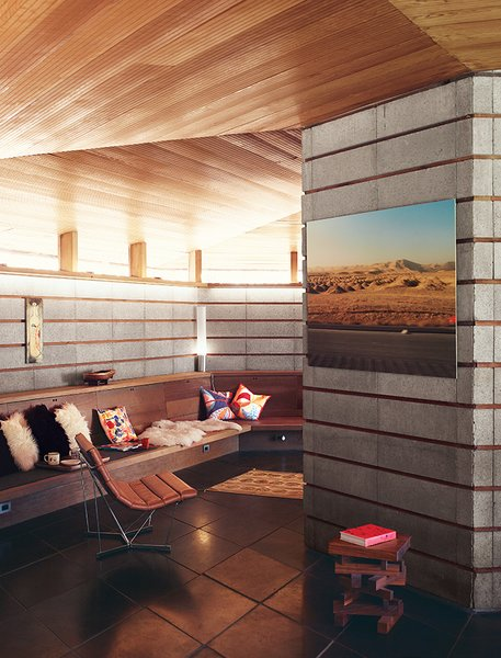 The Midcentury Home That Maintains Its Quirkiness After All These Years - Photo 4 of 9 - A concrete-block wall and a built-in bench line the living room, where a photo by Robbins and a painting by Barry McGee hang near a Catenary chair by George Nelson.