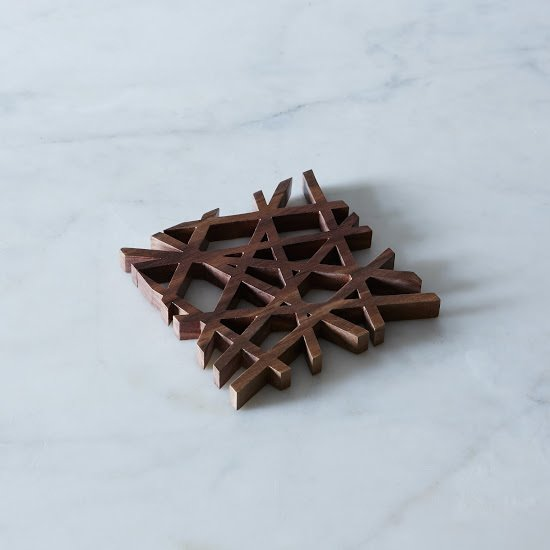 MID-CENTURY MODERN TRIVET $45 – $100  Designed by Fredrick Arndt in eco-friendly American black walnut, this trivet is right up our ally. We love the variation in the wood grain pattern and the sleek and structured design. It's a perfect bit of modernity for the table.  Mid Century by Alex Grossman from Holiday Gift Guide: For The Table