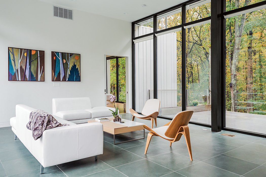 Furnishings inside the home reflect a minimalist sensibility. A Chiva Functional coffee table by BoConcept, a Monti sofa by Dellarobbia, and Hans Wegner Shell chairs by Carl Hansen & Søn outfit the living room.