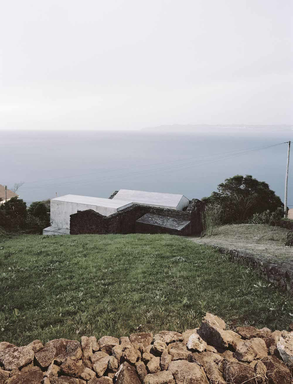 "Initially unassuming, the E/C home appears hidden from the road, perched on the sloping edge of the island and partially wrapped in the basalt walls from an 18th-century farmhouse. Architects Ines Vieira da Silva and and Miguel Vieira approached the site with a vision to create a relationship with the landscape; they designed the 2,600-square-foot holiday home to not only be a simple escape, but also to frame the weathered coast and reflect its past. ""Both paths to the house were designed with basalt stone, as if they were still a rural path,"" Vieira da Silva says. Tagged: Exterior and Concrete Siding Material.  This Modern Coastal Escape Sits Within 18th-Century Stone Walls by Patrick Sisson"