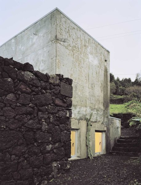 """The new concrete exterior has already been transformed by the rain and humidity of the Azores, and now sports an aged look. The color contrasts with the basalt wall and dark soil of the Ilha Preta (""""Black Island""""). Vieira da Silva anticipates that surprising patterns and textures will develop on the outer walls over time."""