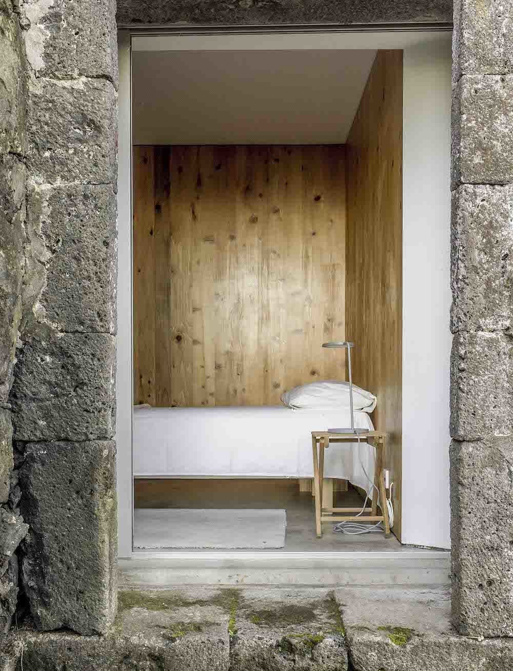 Warm wooden walls ensure the simple bedroom setup, a low mattress next to a Muuto Leaf table lamp, offers more comfort than the cold stone exterior.  Bedrooms by Dwell from This Modern Coastal Escape Sits Within 18th-Century Stone Walls