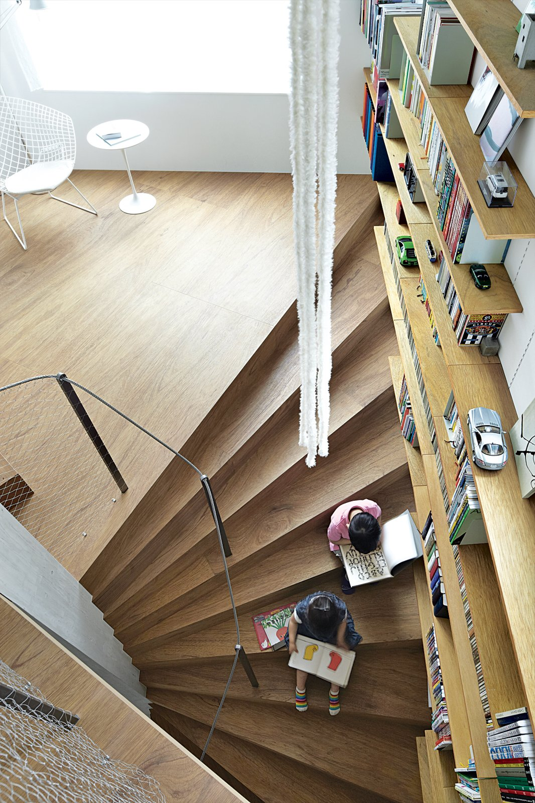 Ran and her brother, Gen, read on one of the structure's 44 continuous steps. Tagged: Staircase, Wood Tread, and Metal Railing.  Photo 1 of 3 in This Sculptural Staircase Shapes an Entire Home