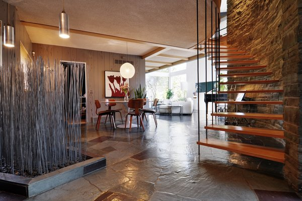 The entrance of the home features slate flagstone flooring and midcentury furniture.