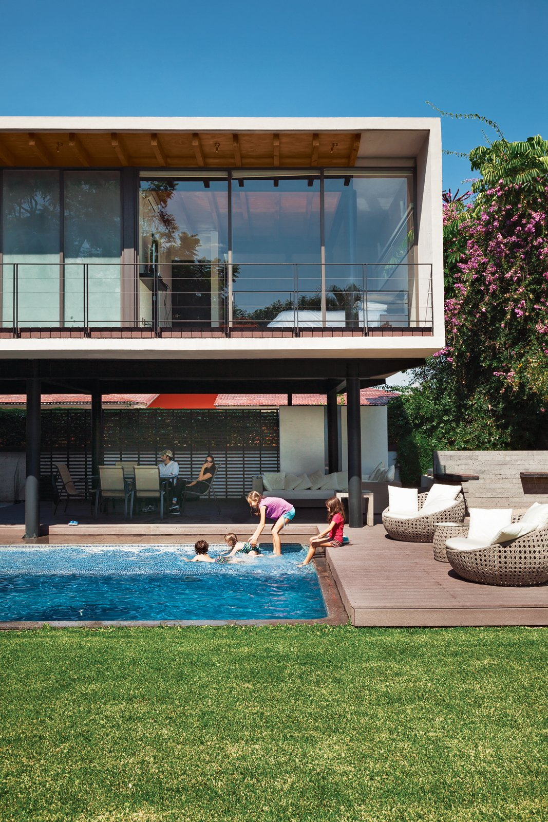 On an idyllic afternoon, members of the Oropeza and Castillo clans splash in the backyard pool framed by Trex decking and outfitted with furniture by Móbica.  Modern Pool Design by Dwell from An Affordable High-Design Vacation Home in Mexico
