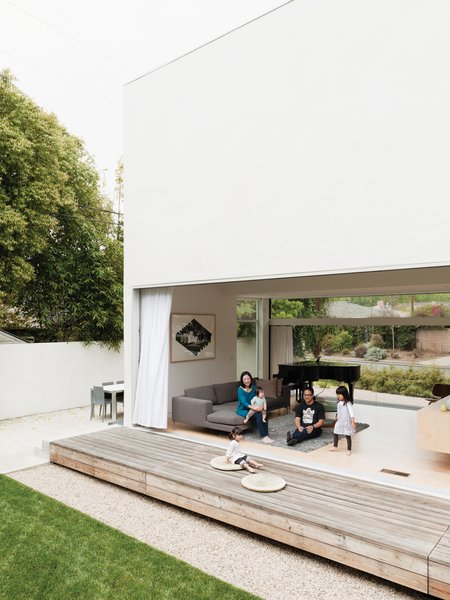 The Lai family—Mayuko, baby Shota on her lap, David, Maya, and Yumi sitting on a cushion on the deck—relaxes in their indoor-outdoor living space, made by opening the glass sliding doors to connect the living room and engawa deck.