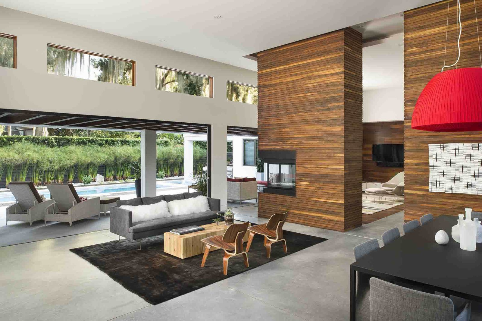 Ipe makes another appearance in the living room, creating a strong indoor-outdoor connection. Kean sited the transom windows to capture views of the moss-covered trees in the backyard.  Photo 3 of 7 in A Modern Home For a Design-Savvy Family in Florida