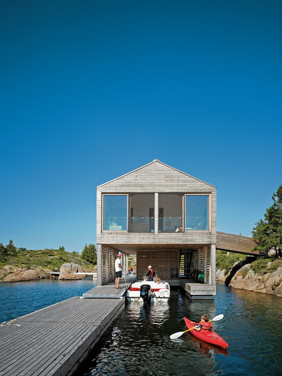 Cedar slats help this Ontario lake house float soundly atop still waters. Photo by: Raimund Koch Tagged: Exterior, House, Boathouse Building Type, and Wood Siding Material.  Best Photos from From Floating Homes to Prefab Moss-Covered Theaters, This Firm's Monograph Has It All