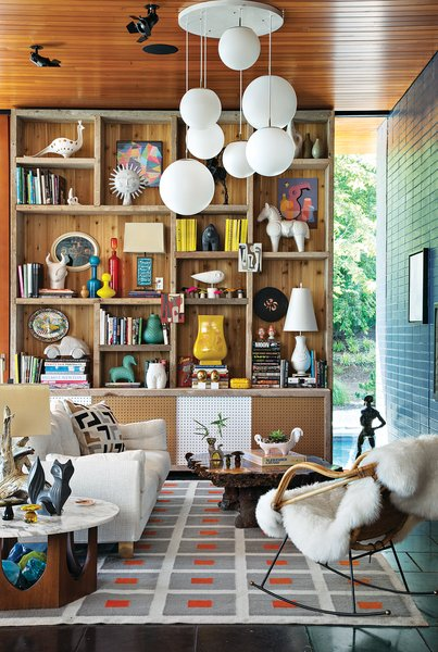 The site-sensitive exterior belies an interior festooned with a kaleidoscopic mix of colors and an array of tactile materials. The Peter rug, Malibu sofa, and ceramics are Adler's own designs. The tables, pendant lights, and rocker are vintage. Adler and Doonan used scaffolding from the house's construction to build the bookshelf.