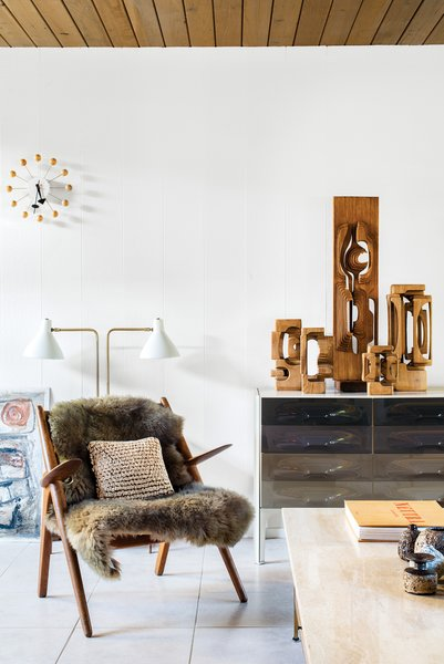 Mark Neely and Paul Kefalides's living room is decked out with the couple's vintage finds, including a Hans Wegner Sawback chair (the fur throw obscures an area needing repair), a George Nelson Ball Clock, a DF-2000 cabinet by Raymond Loewy, a light designed by Greta Von Nessen, and a suite of Brian Willshire wooden sculptures, one of Neely's many collections.
