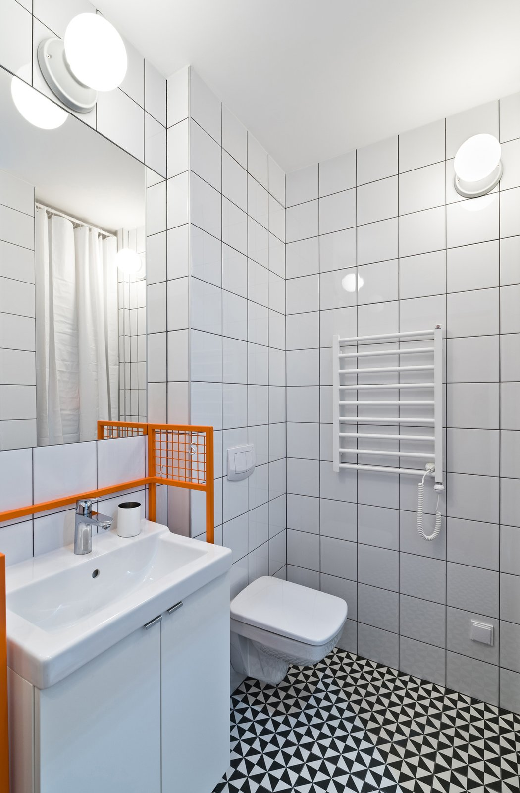 The bathroom features graphic eye-catching Vives floor tiles surrounded by Opoczno wall tiles and clean white plumbing fixtures. The custom-designed orange sink frame adds a whimsical pop of color. Our Dorm Definitely Did Not Look Like This - Photo 6 of 7