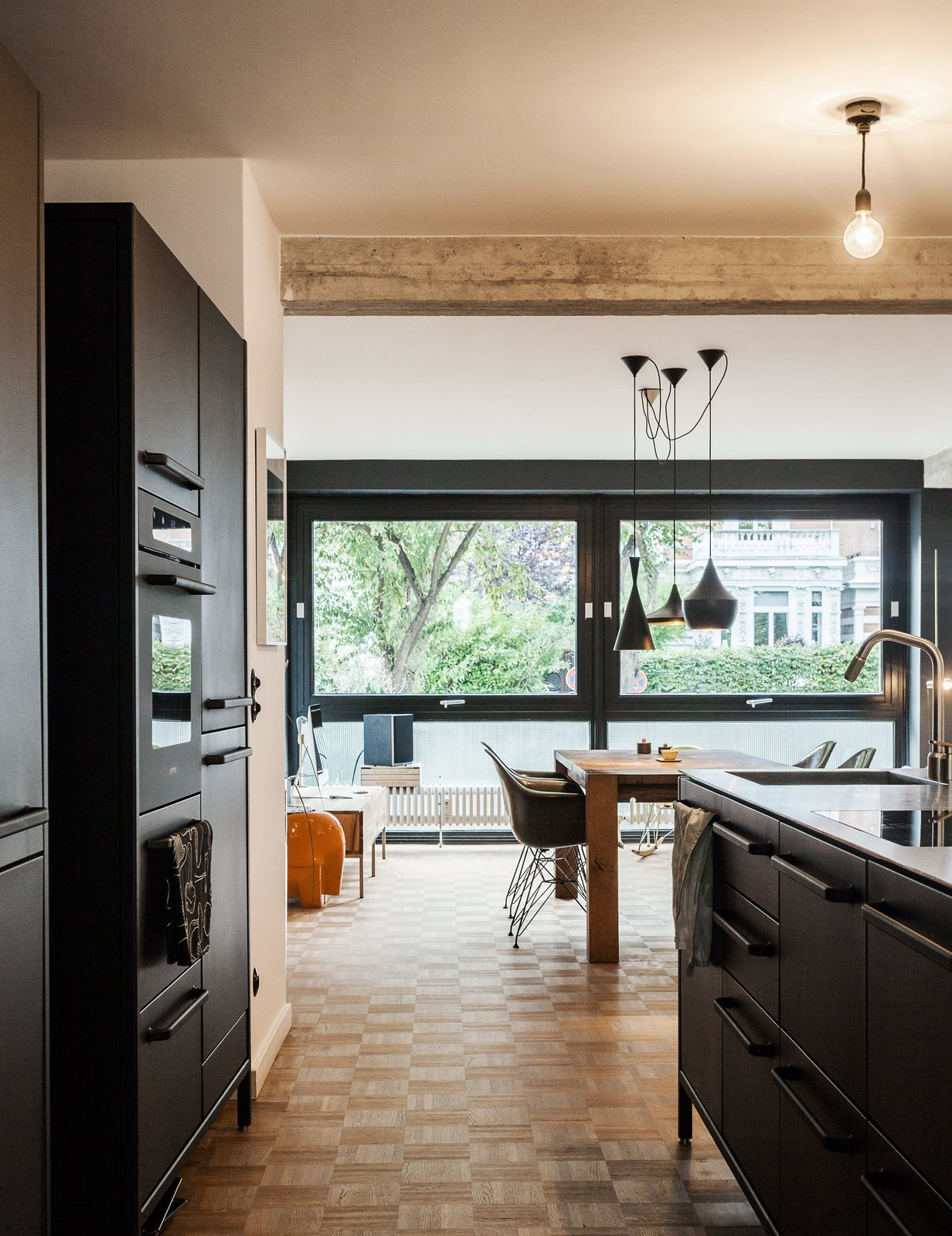 For their kitchen, Fabian and Dorothee Heine selected a steel countertop to contrast the matte-black island and cabinets from Vipp. At mealtimes, the family gathers at a Bigfoot table from e15, which is surrounded by vintage Eames shell chairs. Tagged: Kitchen, Pendant Lighting, Wood Cabinet, and Marble Counter.  Photo 2 of 12 in We Can't Get Enough of This German Apartment's Sleek Matte-Black Kitchen