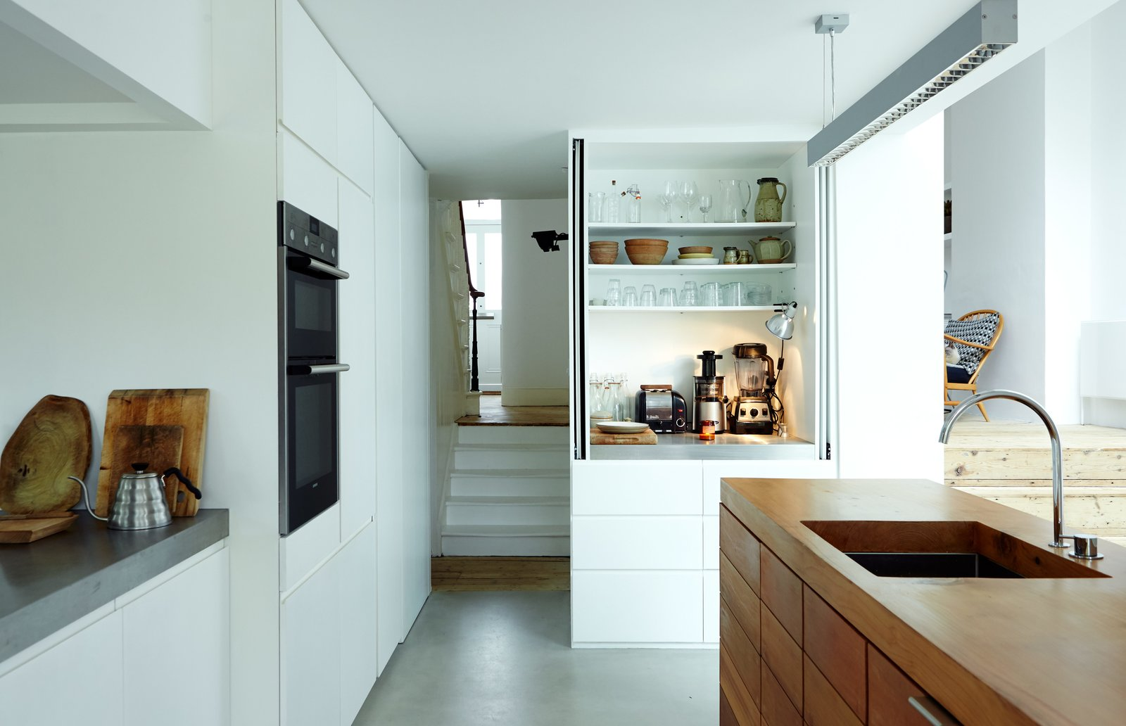 When their house was in need of a pick-me-up, a London couple turned to the designer of their favorite coffee shop for an industrial-strength renovation.  A Lebanese cedar island and stainless-steel countertops provide ample work space—and a place to display treasured items, such as the Buono V60 drip kettle by Hario. The island features a Franke sink with a Vola faucet. The oven is by Siemens and white MDF cabinets stow tools. Tagged: Kitchen, Wood Counter, White Cabinet, and Concrete Floor.  Photo 3 of 6 in Our Editor Sets the Kitchen and Bath Benchmark
