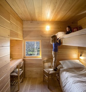 15 Modern and Creative Spaces For Kids - Photo 15 of 15 - The kids' room is wrapped in wood and features built-in bunk beds for a relaxed and cozy camp vibe. It's outfitted with built-in bunk beds.