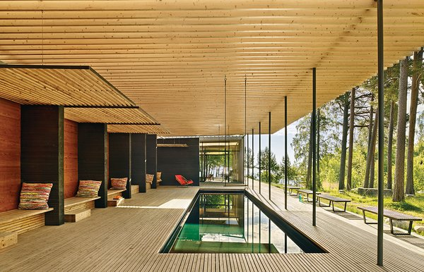 In Sweden, architect Bengt Mattias Carlsson created a pavilion adjacent to a residence dating from the late 1800s. The pergola is made from glue-laminated timber beams set atop steel posts; it protects the pool from falling pine needles. George Nelson benches offer places to sit.