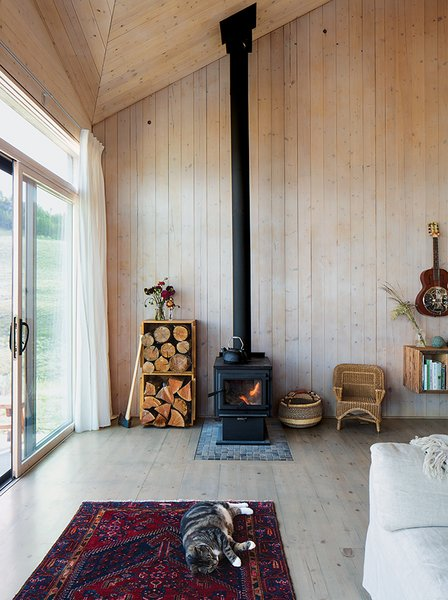 The restrained 820-square-foot interior is defined by the angular ceiling. Garlick left the prefabricated structural panels unfinished to save on material costs. A True North wood stove from Pacific Energy heats the house. Max, the family's cat, naps on a vintage rug purchased on eBay.