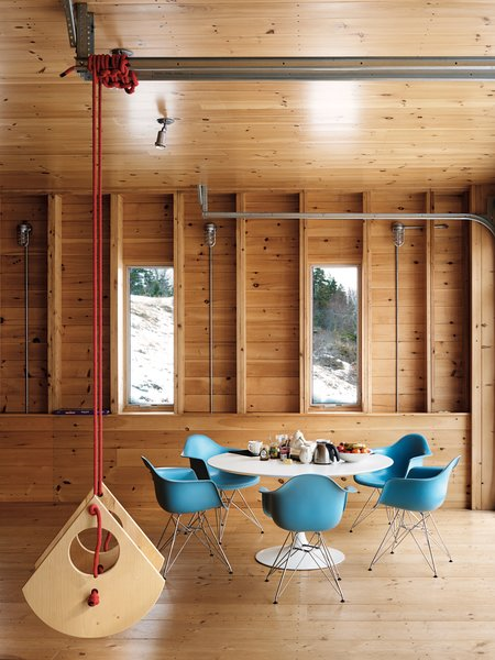 A swing made by architect Christopher Campbell flies high in his Maine retreat alongside modern classics like a Saarinen Tulip table and Eames shell chairs that pop against the wood paneling.