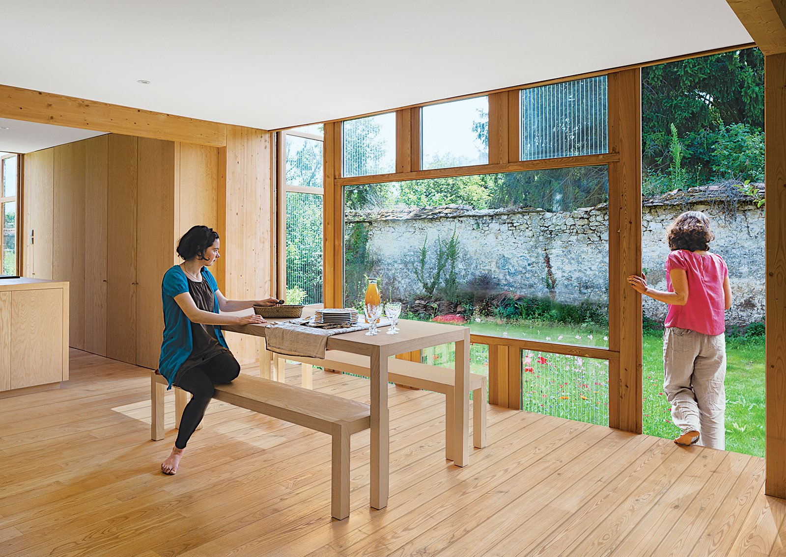 Glass doors printed with a serigraphy technique (above) are on two sides of the house. Jacquot sits at a dining table and benches designed by Arba and built by Menuiserie Ressy.