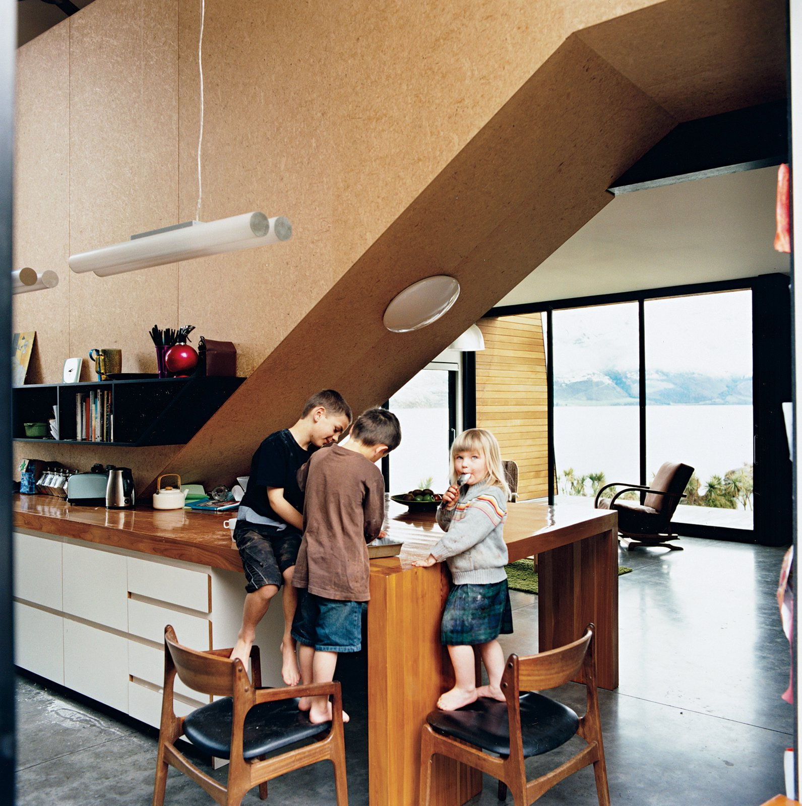 """The kids, Archie, Linus, and Olive, stand in the kitchen, beneath the strand board–clad stairwell that leads to the bedrooms. Kerr and Ritchie initially envisaged rich materials for the interior, but changed their minds in favor of what they call a """"cartoony"""" approach with cheaper, hard-wearing elements. """"We didn't want the space to feel too grown-up,"""" Kerr says."""