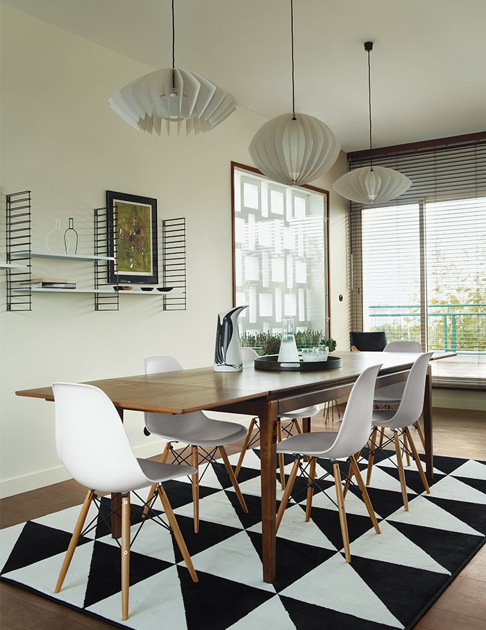 The dining table is from French retailer AM.PM., the pendants are by Him + Her, and the shelves are by Tomado Holland. An Ikea rug echoes the geometric motif found throughout the apartment. Tagged: Dining Room, Pendant Lighting, Chair, Table, Rug Floor, and Medium Hardwood Floor. Best Photos