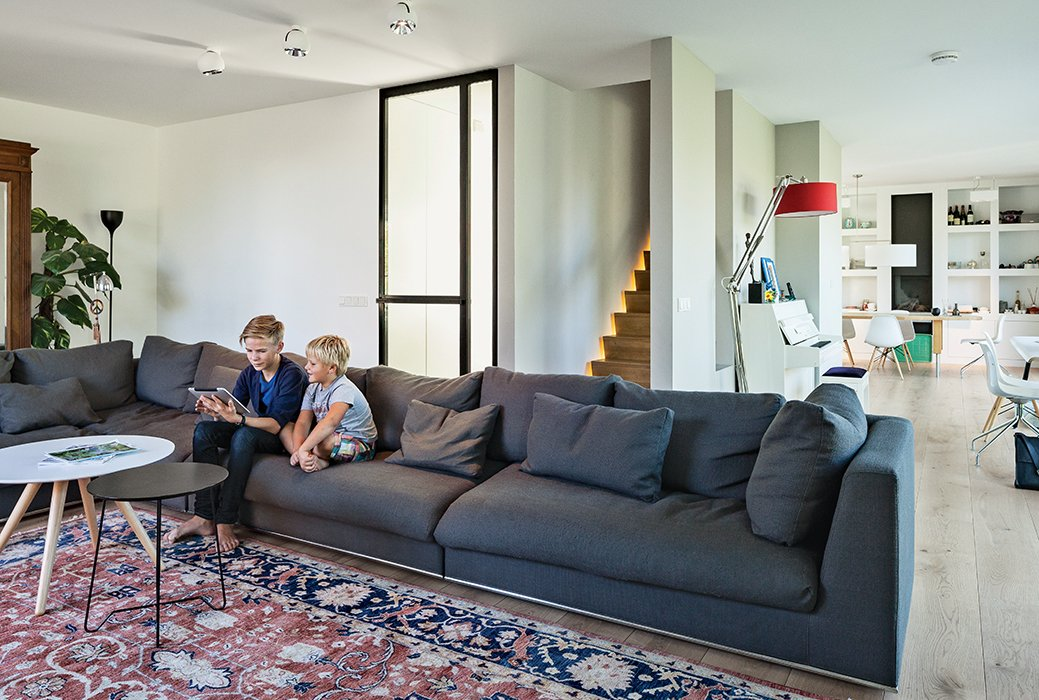 In the living room, Bram and Dirk sit on a sofa by Cocoon near a Persian rug and tables from Leen Bakker. The architects illuminated one side of the stairway leading to the bedrooms.  Photo 10 of 13 in A Modern Take on the Pitched-Roof