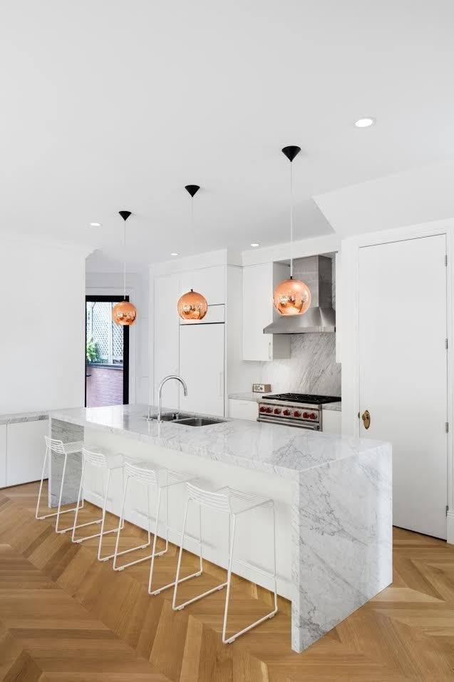 """We placed the kitchen at the center of the house to link with the dining room and the outdoor space,"" Moreau says. In the kitchen, a Wolf oven brings out the silver details in Coit's Bianco Cararra backsplash and island. Hee bar stools by Hay are lined under the island. Tagged: Pendant Lighting.  Photo 20 of 21 in Mad About Marble: 20 Kitchens and Bathrooms"