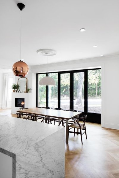 Copper Shade Pendants by Tom Dixon over the island contrast the room's light palette, while a white Flos Skygarden lamp over the dining room table blends into it.