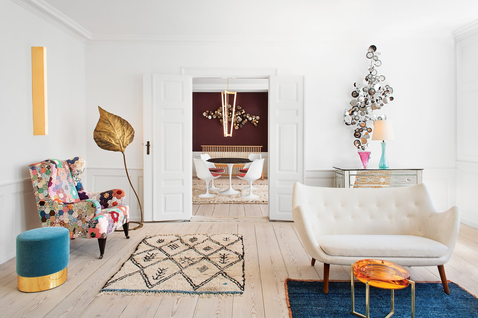 The front parlor is a visitor's first hint of the mix of furniture Tina Seidenfaden Busck has assembled for her showroom the Apartment. A pouffe from Azucena is matched with an array of vintage pieces: a Beni Ourain rug from Morocco, a mirrored chest of drawers from France, and a Finn Juhl Poet sofa. The next room houses a vintage Tulip table and chairs by Eero Saarinen and a Tube Chandelier by Michael Anastassiades. Photos courtesy the Apartment.  100+ Best Modern Seating Designs by Dwell from A Curated Apartment Turned Showroom in Copenhagen