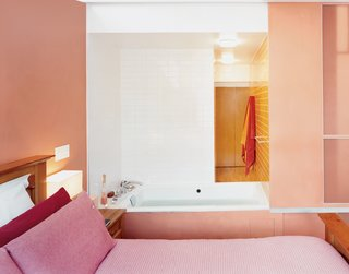 "These 9 Spaces Show How to Rock a Monochromatic Color Scheme - Photo 5 of 9 - In a major renovation and addition to an existing row house in Harlem, Laura Briggs and Jonathan Knowles designed unusual adjacencies, including this hot tub that opens into the master bedroom with sliding panels. The pink bed linens flow into the burnt orange-pink of the walls, which transitions into the orange bathroom beyond. <span style=""color: rgb(204, 204, 204); font-size: 13px;"">Photo by Adam Friedberg</span>"