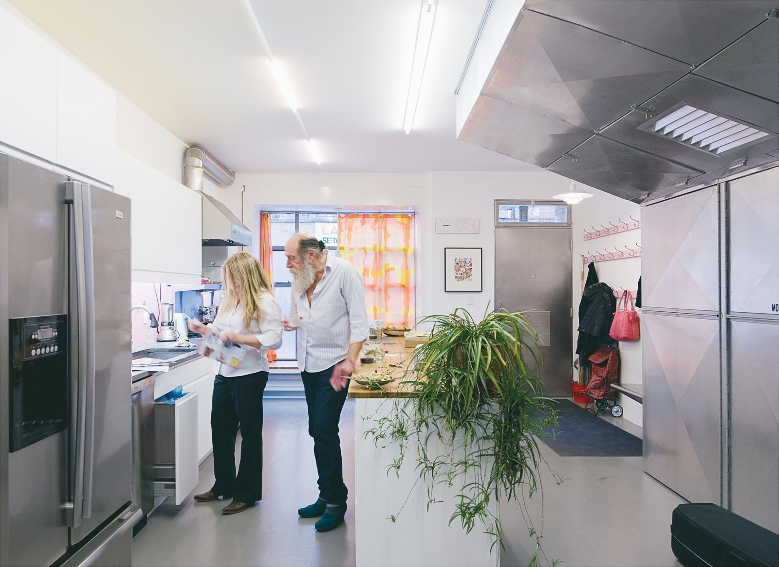 Lawrence and Alice confer in the ground-floor kitchen. Traces of color are visible everywhere, including the orange-and-yellow curtains and pink coathooks. Tagged: Kitchen, Refrigerator, White Cabinet, and Concrete Floor.  Photo 5 of 13 in Village People