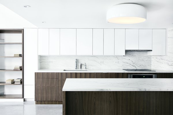 In the sleek kitchen, the white Ikea cabinet uppers seem to disappear into the wall, while the bases get a distinctive custom walnut wrapping. Flanking the cabinets are open bookshelves, which provide secondary function as a spacial divider for the children's play area. A Dornbracht faucet sits on a slab of Vermont Olympian White Danby marble, which is also used for the island and backsplash.