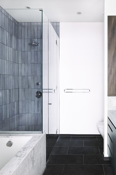 The ensuite master bathroom features Ann Sacks slate floor tile, contrasted with white Carrara marble that wraps the Kohler Tea for Two tub. The shower features tile from Heath Ceramics.