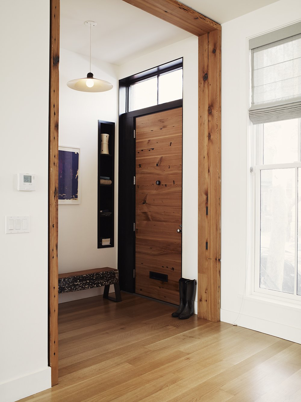 A common theme of the remodel was the incorporation of salvaged material, both from the original house and outside sources. Collaborating with Peter Buley of Analog Modern, the original hemlock fir joists of the house were repurposed into the main entry door. Adjacent to the door is a bench made from a heart pine beam, sourced by Buley. The beam had been charred during a circa-1900 fire, and subsequently painted over during the last 100 years. The unique piece now finds its home in the entry foyer. Tagged: Doors, Wood, Swing Door Type, and Exterior.  Photo 3 of 8 in 8 Beautiful Home Projects Using Reclaimed Wood from It's Back to Basics for This 1901 Brooklyn Town House