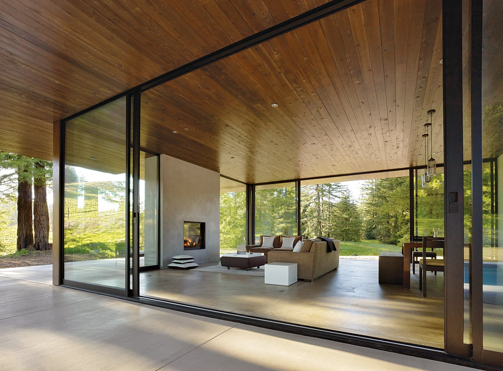 """Creating efficient space is valuable, but for us, rooms that offer visual and spatial continuity with nature are also important,"" architect Julie Dowling explains. ""When the sliding doors are open, the living room and kitchen double in size."" Tagged: Living Room, Concrete Floor, Sofa, and Standard Layout Fireplace.  Photo 2 of 5 in This Couple Achieves Their Glass House Goals"