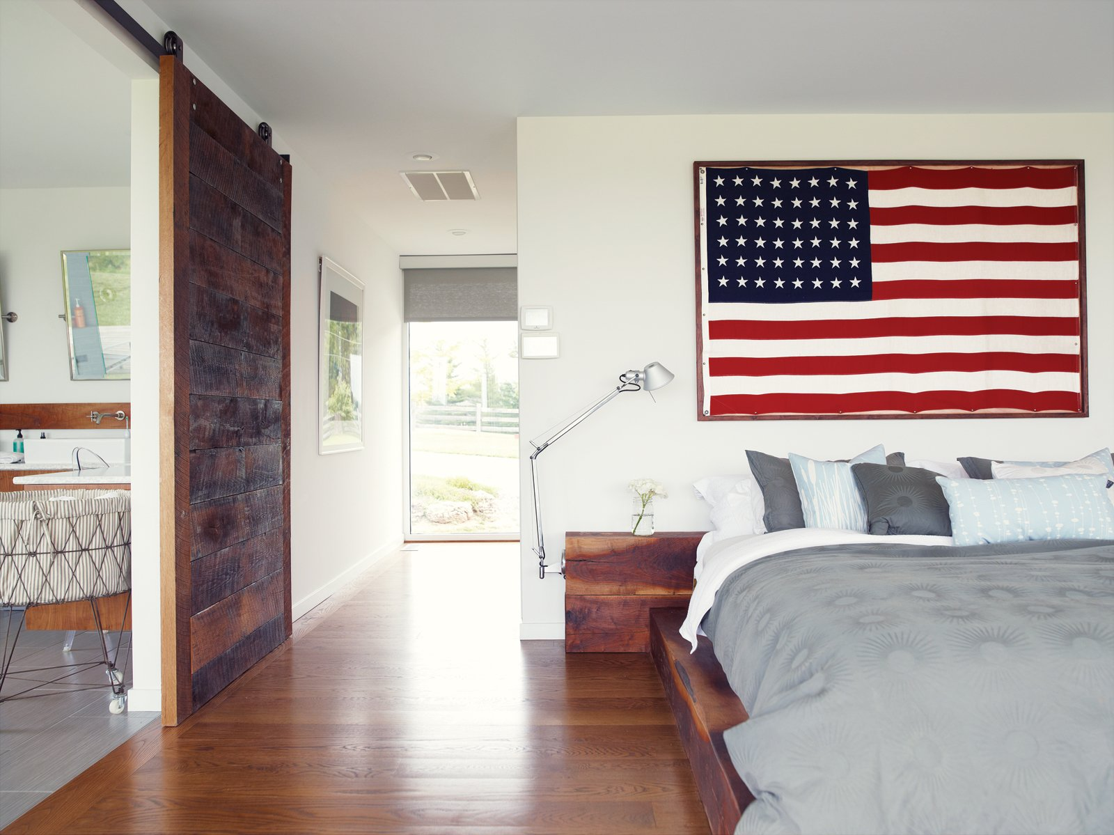 He built the walnut bed and nightstands in the master bedroom with the help of Hannah's two brothers. One of his clients at his hair salon gave him the American flag; the bedside lights are Tolomeo classic wall lamps by Artemide. The bed linens are   from Inhabit. A sliding barn door rolls sideways to reveal the bathroom.